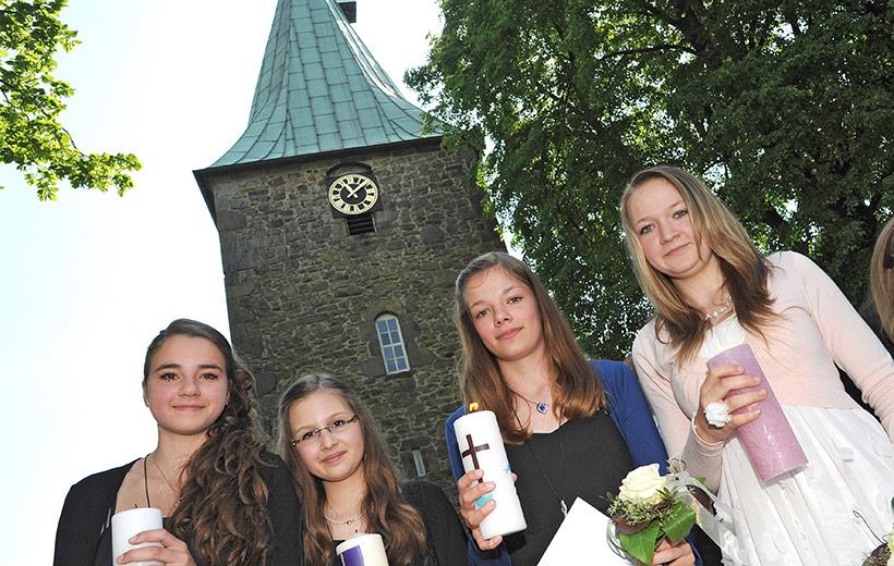 Konfirmanden stehen vor der Kirche