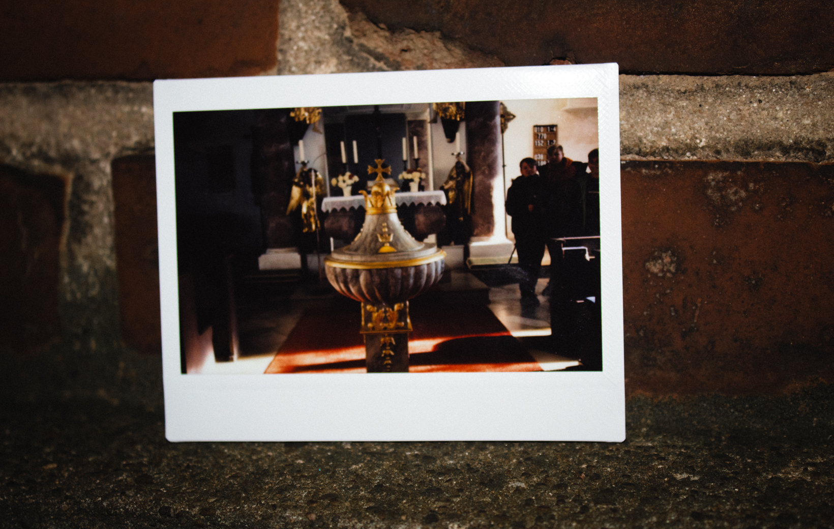 Das Bild zeigt ein Polaroid von einem Taufbecken
