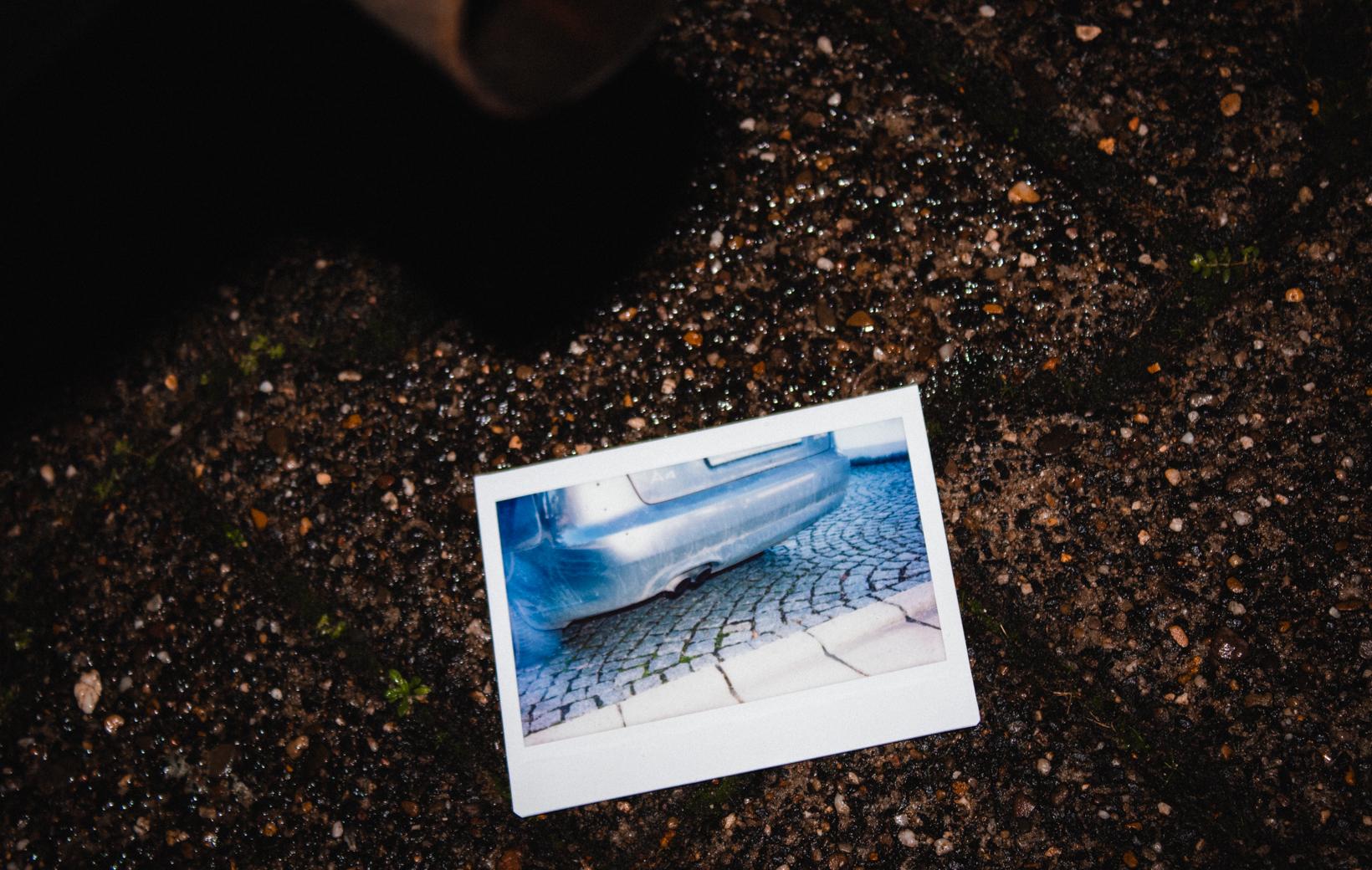 Das Bild zeigt ein Polaroid von einem Auto-Auspuff