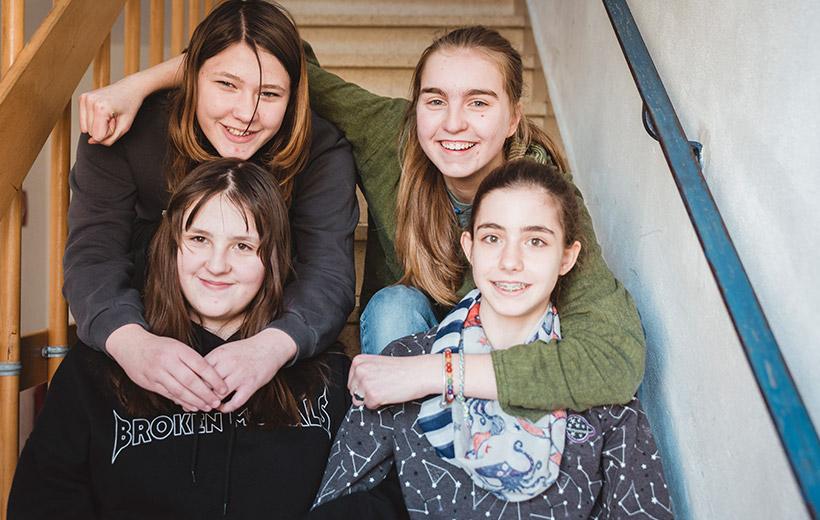 Das Bild zeigt Jula und ihre Freundinnen in einem Treppenhaus